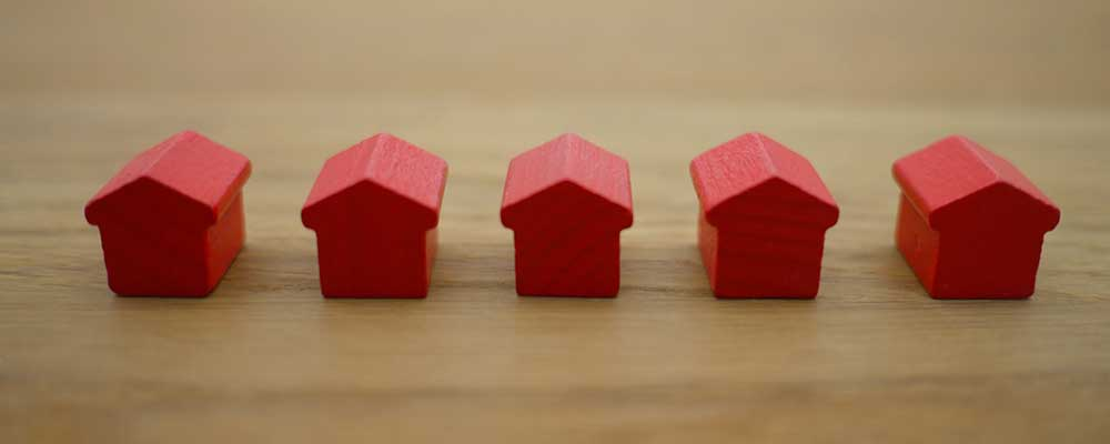 Five tiny red houses on a table top representing mortgages